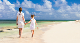 Back view family mother and daughter walking at beach enjoying tropical summer vacation